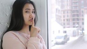 沈默请,有手指的年轻亚裔妇女在嘴唇,坐在窗口 影视素材