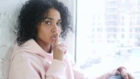 沈默请,有手指的年轻非洲妇女在嘴唇,坐在窗口 股票录像