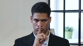 沈默姿态由黑商人,在嘴唇的手指的 股票视频
