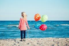 沉思与五颜六色的束的少年白色白种人儿童孩子画象气球,站立在日落的海滩 图库摄影