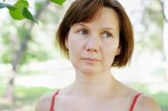 沉思中年妇女 免版税库存图片