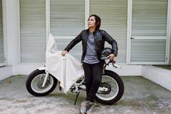 沉思亚裔摩托车骑士 免版税库存照片