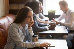 沉思单独坐在咖啡馆的桌上的翻倒女孩 免版税库存照片