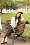 沉思和典雅的美丽的妇女坐老长凳 免版税库存照片