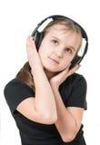 沉思地查寻女孩的少年听到与大耳机的音乐和 库存照片
