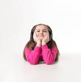 沉思地查寻女孩的少年听到与大耳机的音乐和 免版税图库摄影
