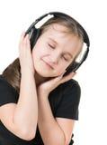 沉思地查寻女孩的少年听到与大耳机的音乐和 库存图片