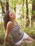 年轻沉思女孩在夏天森林里 库存照片