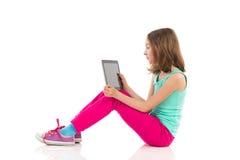 沉思女孩坐与一种数字式片剂的地板 免版税库存图片