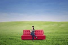 沉思女性食用在室外红色的沙发的咖啡 免版税库存照片