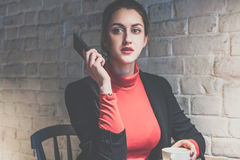 年轻沉思妇女在咖啡馆在桌和饮料咖啡上,当谈话坐电话时 女孩是生气听见新闻 免版税图库摄影