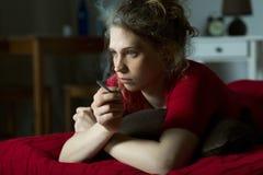沉思妇女抽烟的香烟 免版税库存照片