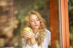 沉思妇女饮用的咖啡在家,看窗口 免版税库存图片