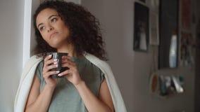 沉思妇女饮用的咖啡或茶画象在家 免版税库存图片