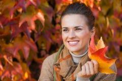沉思妇女画象有叶子的在秋天叶子前面 免版税库存照片