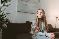 沉思孩子女孩坐单独沙发 免版税库存照片
