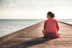 沉思少妇游人享有她的生活坐与无限视图拷贝空间的码头海滩 免版税库存图片