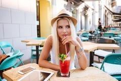 沉思少妇饮用的鸡尾酒和认为在室外咖啡馆 免版税库存照片