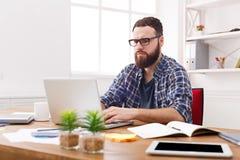 沉思年轻商人与膝上型计算机一起使用在现代白色办公室 库存照片