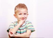 沉思微笑的白肤金发的男孩儿童孩子画象在桌上 免版税库存图片