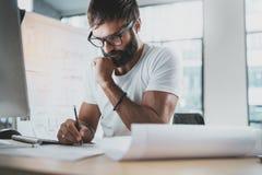 沉思有胡子的设计师佩带的眼睛玻璃和白色T恤杉,运转在现代顶楼演播室办公室 人图画scetches 免版税库存照片