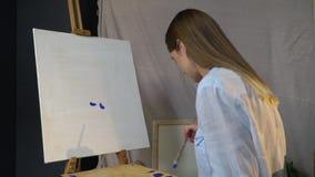 沉思深色的艺术家做第一污迹蓝色油漆在站立一艘白色的废船在一个木画架 股票录像