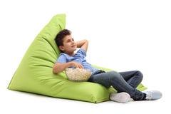 沉思男孩坐装豆子小布袋 免版税库存图片