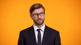沉思男性考虑开始的企业想法,橙色背景 免版税库存图片