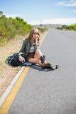 沉思白肤金发的妇女坐路旁 免版税库存照片