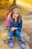 沉思白肤金发的孩子的女孩不耐烦在室外的森林里 免版税库存照片