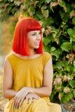 沉思红发妇女在公园 库存照片