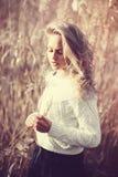 沉思美丽的年轻白肤金发的女孩画象一个领域在白色套头衫,健康的概念和秀丽的 免版税库存照片
