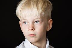 沉思英俊的矮小的白肤金发的男孩 图库摄影