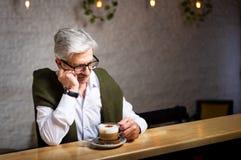 沉思资深喝咖啡在酒吧 免版税图库摄影