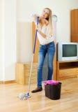 沉思长发妇女洗涤的镶花地板 免版税库存照片