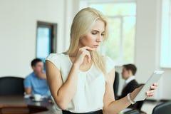 沉思年轻女商人画象有片剂计算机的 免版税库存照片