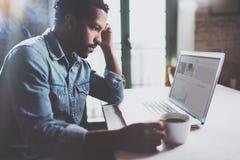 沉思年轻非洲在膝上型计算机的人读的financical新闻,当喝无奶咖啡在晴朗的早晨时 概念  免版税库存照片