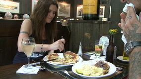 沉重刺字食人与吃薄饼的妇女的一个三明治在餐馆 股票视频