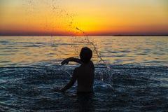 沐浴在海的少年男孩在日落在西西里岛 免版税图库摄影