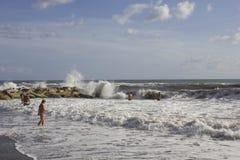 沐浴在风大浪急的海面的人们 免版税库存照片
