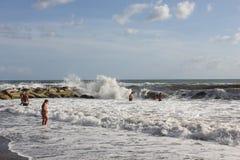 沐浴在风大浪急的海面的人们 免版税库存图片