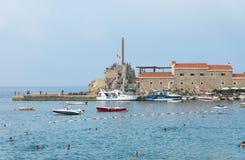 沐浴人和游船在Petrovac,黑山 库存图片