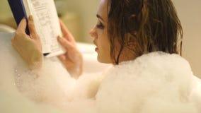 沐浴和读书的可爱的少妇在有泡沫的浴盆 股票视频