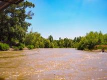 沐浴在一条凉快的河的少年演奏和获得乐趣在热的夏天太阳下 免版税库存图片
