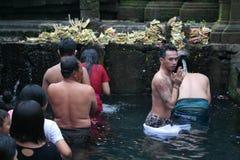 沐浴在圣水寺庙Tirta Empul巴厘岛的崇拜者 免版税库存照片
