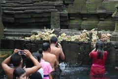沐浴在圣水寺庙Tirta Empul巴厘岛的崇拜者 免版税库存图片