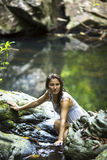 沐浴在小河的美丽的妇女在瀑布附近 免版税图库摄影
