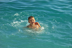 沐浴在海或海洋温暖的晴天的青少年的男孩 免版税图库摄影
