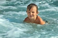 沐浴在海的小男孩五在一个晴天 库存照片