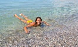 沐浴在清楚的海的美丽的妇女比基尼泳装 免版税库存照片